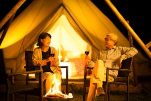 グランピングテントの前で談笑をするシニア夫婦の写真素材 [FYI02682996]