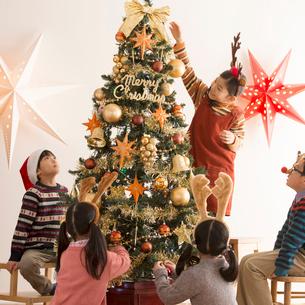 クリスマスツリーに飾り付けをする子供達の写真素材 [FYI02683009]