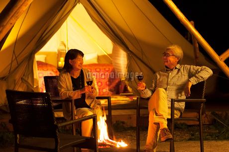 グランピングテントの前で談笑をするシニア夫婦の写真素材 [FYI02683024]