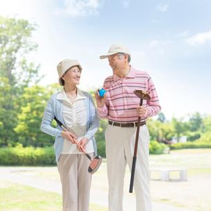グラウンドゴルフのクラブを持って立つシニア夫婦の写真素材 [FYI02683205]