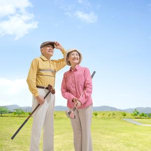 グラウンドゴルフのクラブを持って立つシニア夫婦の写真素材 [FYI02683206]