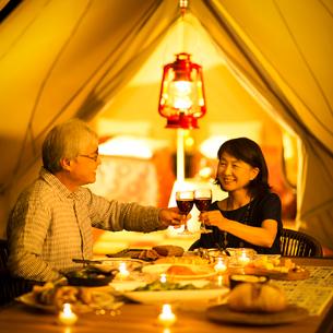 グランピングテントの前で乾杯をするシニア夫婦の写真素材 [FYI02683297]