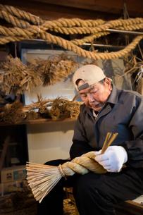 冬の農閑期にしめ縄作りする80代男性の写真素材 [FYI02683376]
