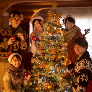 クリスマスツリーに飾り付けをする若者たちの写真素材 [FYI02683484]
