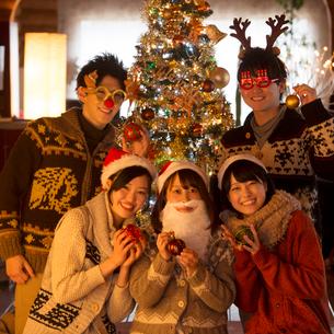 クリスマスツリーの周りで微笑む若者たちの写真素材 [FYI02683494]