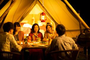 グランピングテントの前で談笑をする若者たちの写真素材 [FYI02683504]