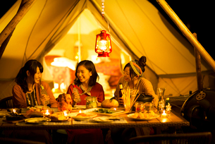 グランピングテントの前で談笑をする若者たちの写真素材 [FYI02683523]