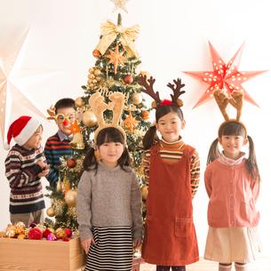 クリスマスツリーの前で微笑む子供達の写真素材 [FYI02683593]