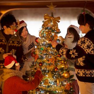 クリスマスツリーに飾り付けをする若者たちの写真素材 [FYI02683615]