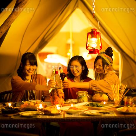 グランピングテントの前で乾杯をする若者たちの写真素材 [FYI02683632]