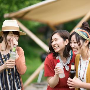 グランピングテントの前で談笑をする若者たちの写真素材 [FYI02683827]