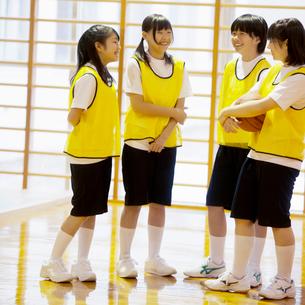 体育館で談笑をする女子学生の写真素材 [FYI02683830]