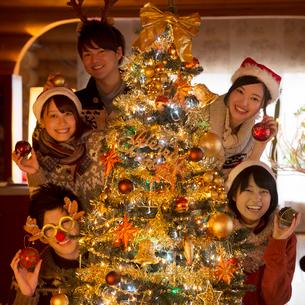 クリスマスツリーの周りで微笑む若者たちの写真素材 [FYI02683831]