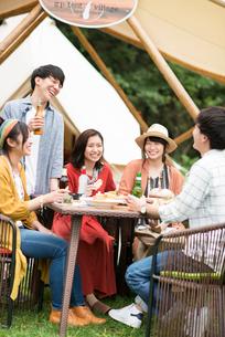 グランピングテントの前で談笑をする若者たちの写真素材 [FYI02683843]