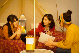 グランピングテントの中で談笑をする若者たちの写真素材 [FYI02683867]