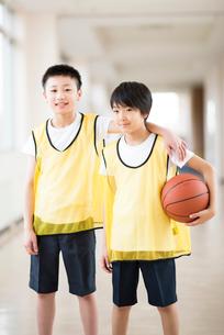 廊下でバスケットボールを持ち微笑む小学生の写真素材 [FYI02683884]