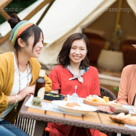 グランピングテントの前で談笑をする若者たちの写真素材 [FYI02683902]