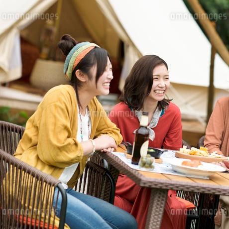 グランピングテントの前で談笑をする若者たちの写真素材 [FYI02683931]