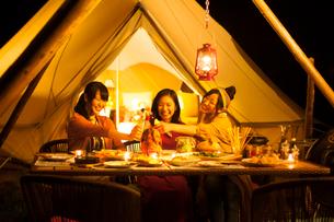 グランピングテントの前で乾杯をする若者たちの写真素材 [FYI02683933]
