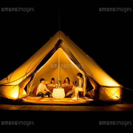 グランピングテントの中で談笑をする若者たちの写真素材 [FYI02683955]