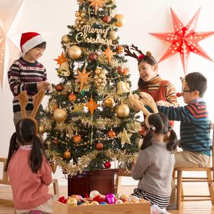 クリスマスツリーに飾り付けをする子供達の写真素材 [FYI02684024]