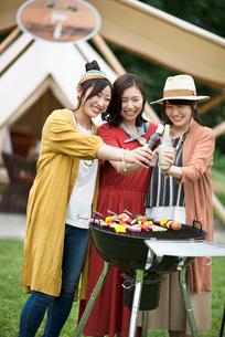 グランピングテントの前で乾杯をする若者たちの写真素材 [FYI02684126]