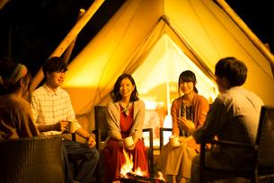 グランピングテントの前で談笑をする若者たちの写真素材 [FYI02684160]