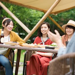 グランピングテントの前で談笑をする若者たちの写真素材 [FYI02684307]