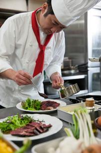 ステーキを皿に盛り付ける調理師の写真素材 [FYI02684661]