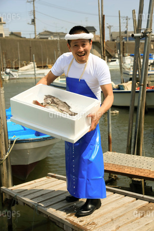 港でトロ箱を抱える鮮魚店店員の写真素材 [FYI02684848]