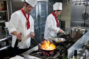 ステーキをフライパンでフランベする調理師の写真素材 [FYI02684925]