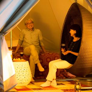 グランピングテントの中で談笑をするシニア夫婦の写真素材 [FYI02684962]
