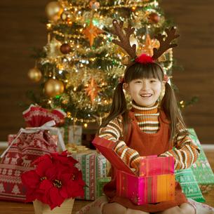 クリスマスプレゼントを開ける女の子の写真素材 [FYI02684981]