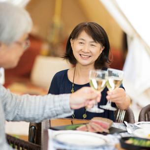 グランピングテントの前で乾杯をするシニア夫婦の写真素材 [FYI02685022]
