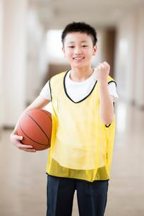 廊下でバスケットボールを持ちガッツポーズをする小学生の写真素材 [FYI02685024]