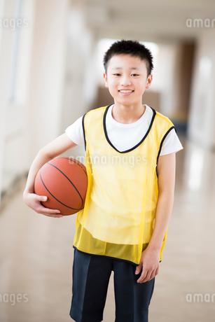 廊下でバスケットボールを持ち微笑む小学生の写真素材 [FYI02685045]