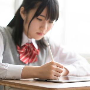 タブレットPCで勉強をする女子学生の手元の写真素材 [FYI02685063]