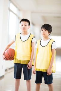 廊下でバスケットボールを持ち真剣な表情をする小学生の写真素材 [FYI02685065]