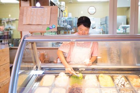 アイスクリームを作る20代女性店員の写真素材 [FYI02685087]