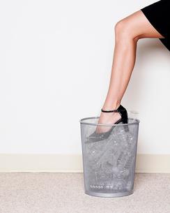 Woman crushing plastic bottles by footの写真素材 [FYI02685236]
