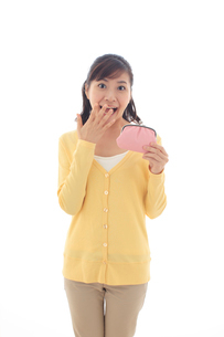財布を持ちポーズをとる女性の写真素材 [FYI02685271]