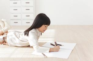 スケッチブックに色鉛筆で絵を描く女の子の写真素材 [FYI02685371]