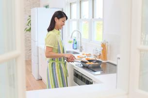 明るいキッチンで料理をする女性の写真素材 [FYI02685484]