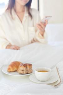 広いベッドルームで携帯を見ながら朝食を食べる女性の写真素材 [FYI02685533]