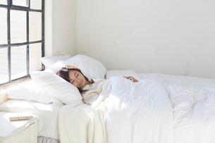 大きな窓のある広い寝室で眠る女性の写真素材 [FYI02685550]