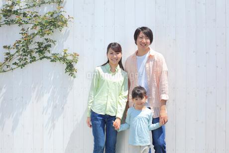 白い板壁の前に並ぶ3人家族の写真素材 [FYI02685551]