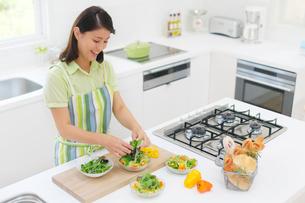 明るいキッチンで料理をする女性の写真素材 [FYI02685557]