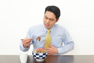 食事中に胃もたれを感じる男性の写真素材 [FYI02685606]
