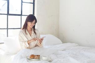 広いベッドルームで携帯を見ながら朝食を食べる女性の写真素材 [FYI02685607]