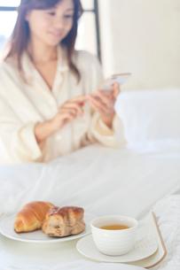 広いベッドルームで携帯を見ながら朝食を食べる女性の写真素材 [FYI02685643]